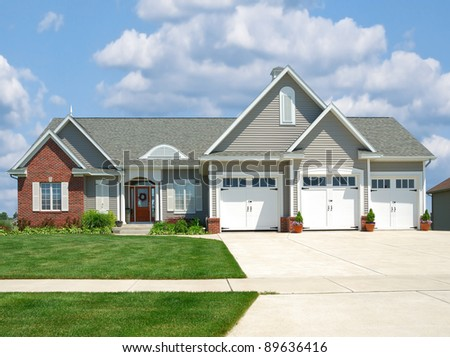 Modern brick and vinyl siding house in the suburbs with a three car garage in summer. - stock photo