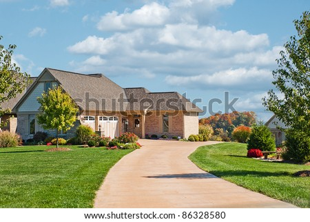 Modern brick, stone and shakes two story house in USA with a concrete driveway leading to a side entry garage in autumn. - stock photo