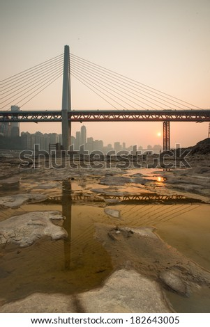 Modern bridge at sunset time with city background - stock photo