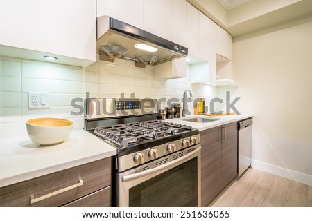Modern, bright, clean, kitchen interior with stainless steel appliances in a luxury apartment. - stock photo