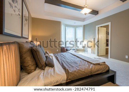 Modern bright master bedroom interior with designer pillows in a luxury house, hotel. - stock photo