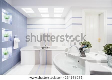 Modern bright toilet interior with white tiles - stock photo