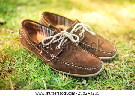 Modern brown leather men's shoes, elegant summer moccasins in grass. Men fashion, men accessories and footwear.  - stock photo