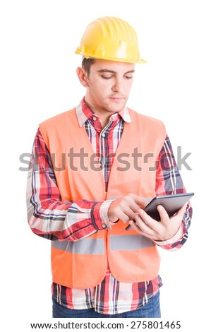 Modern builder using wireless tablet to check architecture plans - stock photo