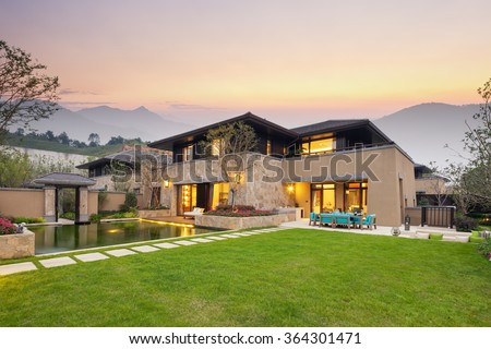 modern building by the fishpond and beautiful meadow in colorful sky at twilight - stock photo