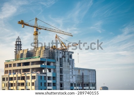 Modern building condominium under crane construction against blue sky - Bangkok Thailand - stock photo