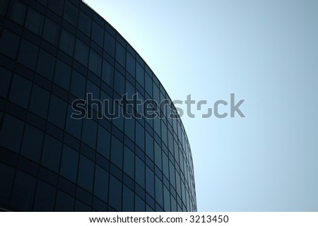 Modern building curves into a blue sky - room for text on right hand side - stock photo