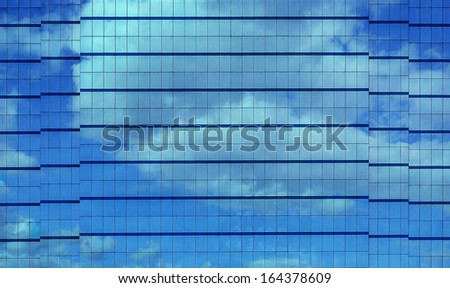 Modern Building Facade with Reflection of Clouds and Sky - stock photo