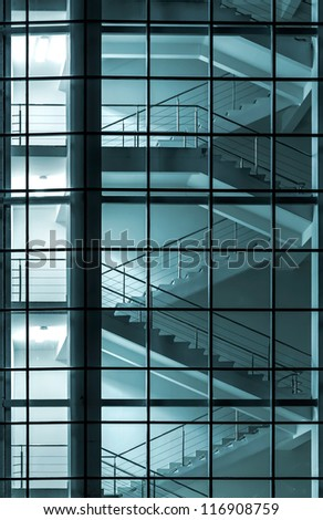 Modern building facade with staircase behind a transparent glass wall - stock photo