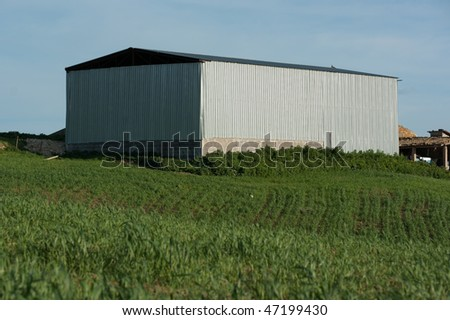 modern building for storage the fodder or the agricultural equipment in a green meadow - stock photo