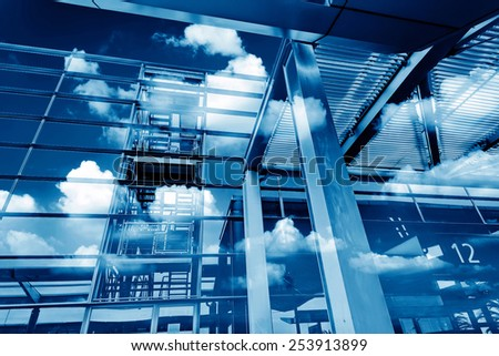 Modern building glass facade and reflection clouds - stock photo
