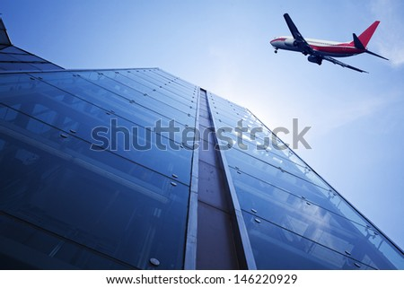 Modern building glass wall. Aircraft in the sky - stock photo