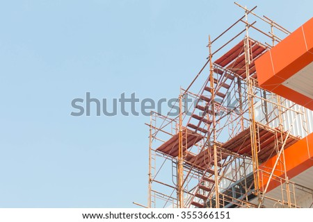 Modern building is under construction, metal scaffolding and sky - stock photo