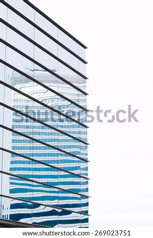 Modern building mirror facade in blue tone - stock photo