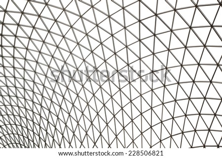 Modern building with curving roof and glass steel column. A triangular mesh roof, truss - stock photo