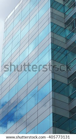 Modern building with glass windows reflected sky in vertical format