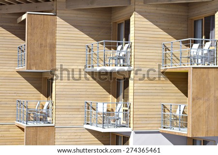 Modern building with lines of balconies and furniture. - stock photo