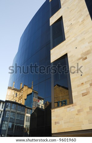 Modern building with the reflection of an old building in the tinted glass - stock photo