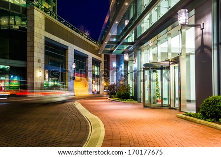 Modern buildings at night along a street in Baltimore, Maryland. - stock photo