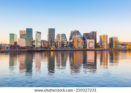Modern buildings in Oslo, Norway, with their reflection into the water. These are some of the new buildings in the neighbourhood of Bjorvika. Concepts of travel and architecture. - stock photo