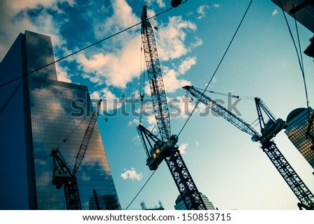 Modern buildings with cranes at sunset. Urban concept - stock photo