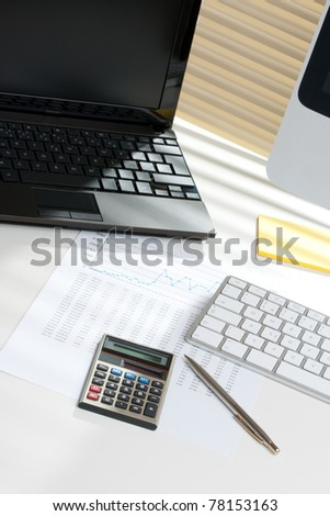 Modern business analyst workplace with laptop and computer - stock photo