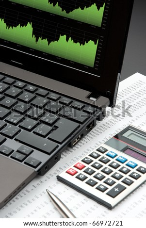Modern business and stock market analyze with laptop, calculator, pen and printed data sheet - stock photo