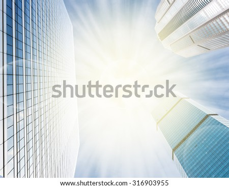 Modern business building glass of skyscrapers on blue sky background with sun light, Business concept of architecture - stock photo