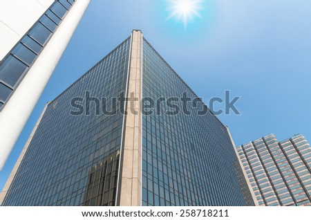 Modern business building glass of skyscrapers with sun - stock photo