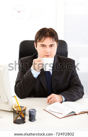 Modern business man sitting at office desk and drinking coffee