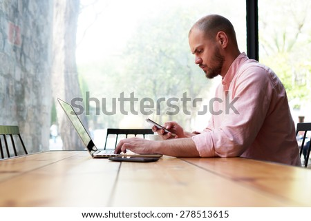 Modern business man using smart phone and laptop computer in light loft interior, young hipster busy using smart phone at office desk, male student typing message on phone at wooden coffee shop table - stock photo