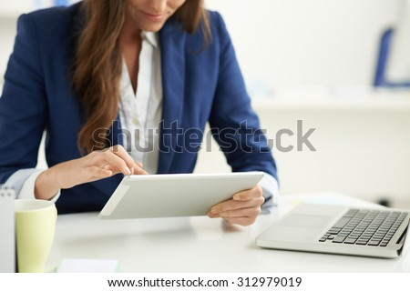 Modern business: manager using tablet computer her workplace - stock photo