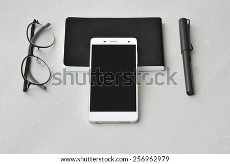 Modern business on the go- smart phone, notebook,  eyeglasses, and pen, isolated - stock photo