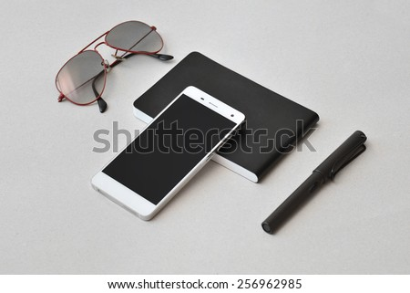 Modern business on the go-  smart phone, notebook, sunglasses, and pen, isolated - stock photo