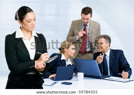 Modern business team taking notes and discussing together their business strategy at meeting in office - stock photo