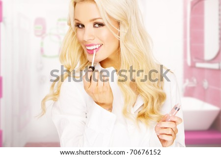 modern business woman applying makeup in pink bathroom - stock photo