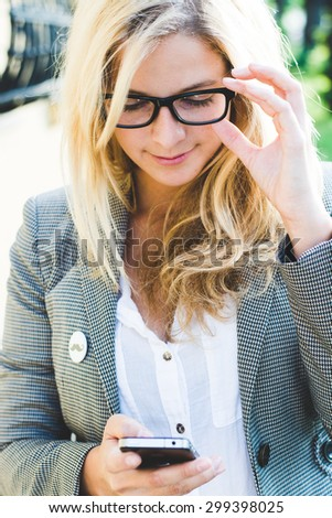 Modern business woman using phone outdoor - stock photo