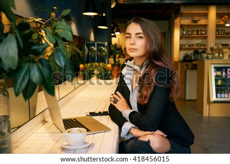 modern business woman waiting for people at a cafe to spend an interview with him. attractive girl using a laptop and a smartphone for work on a new business project. - stock photo