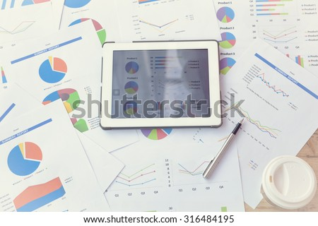 Modern business workplace with business news website on digital tablet, coffee and some charts and graphs on a desktop. - stock photo