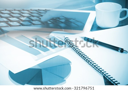 Modern business workplace with computer and digital tablet, mobile banking on a smartphone and some charts and graphs on a desktop. - stock photo