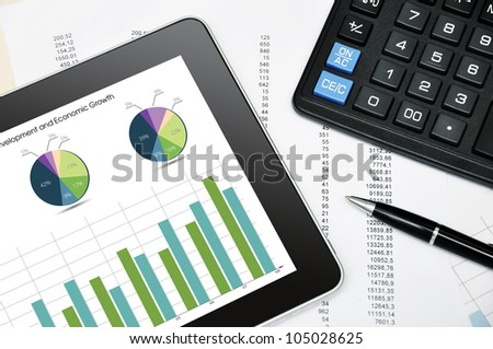Modern business workplace with digital tablet, calculator, pen and printed data sheet - stock photo