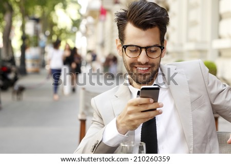 Modern businessman and business woman sitting at coffee shop and using mobile. Business people. - stock photo