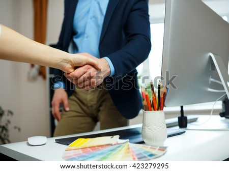 Modern businessman and businesswoman shaking hands in office