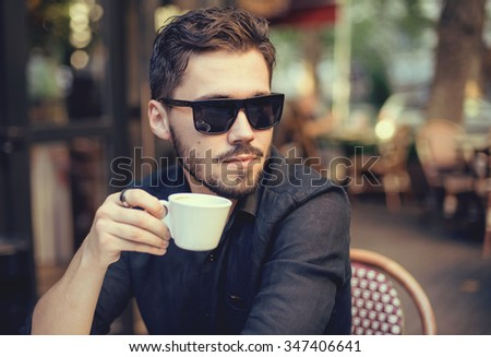 Modern businessman drinking coffee at coffee shop on the sunset. - stock photo