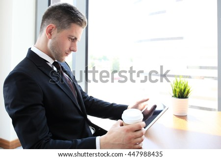 Modern businessman drinking coffee in the office cafe during lunch time and using tablet - stock photo