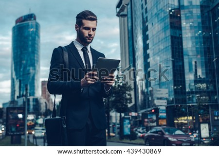 Modern businessman. Night time image of confident young man in full suit holding digital tablet and looking at it while standing outdoors with cityscape in the background - stock photo