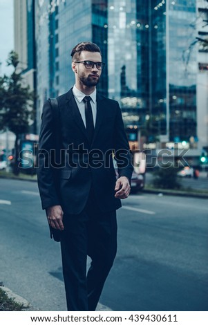 Modern businessman on the go. Night time image of confident young and handsome man in full suit walking along the street with cityscape in the background