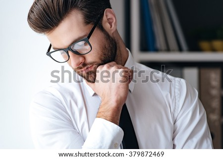Modern businessman. Portrait of handsome young businessman in glasses looking down and keeping hand on chin while standing in office - stock photo