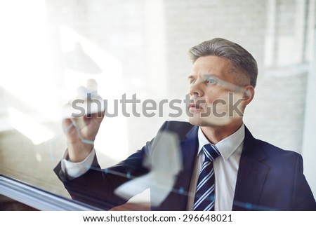 Modern businessman standing by transparent board