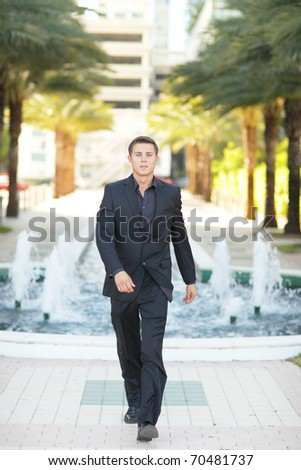 Modern businessman walking towards the camera - stock photo